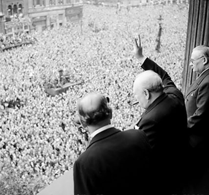 Winston Churchill waving to crowds in Whitehall, London on the day he confirms that the war with Germany was over
